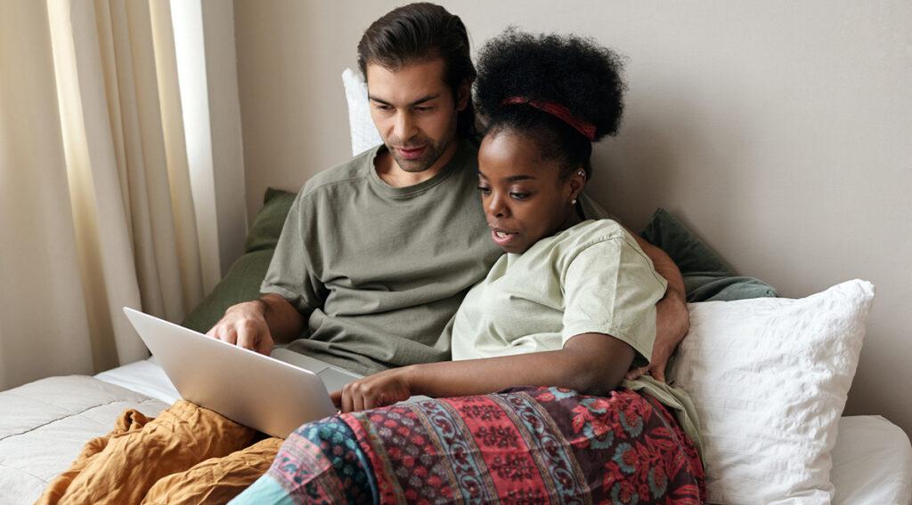 Mann und Frau mit Laptop im Bett